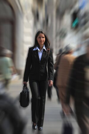 significant: Businesswoman walking quickly in a crowded downtown.The image presents a significant spin blur effect to accentuate the dynamism of the scene. Stock Photo