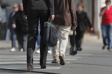 cros: Image of a businesswomans lower body. She is carrying a computer bag while crossing the street in a city.  Stock Photo