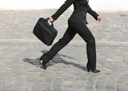 stride: Businesswomans legs, as she is walking in a hurry along a cobbled street.