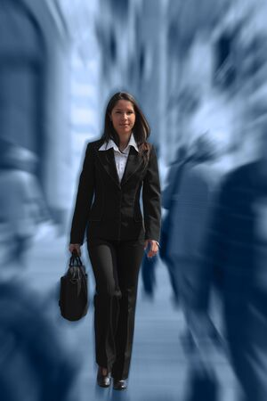 dynamic motion: Businesswoman walking quickly in a crowded downtown.The image presents a significant spin blur effect to accentuate the dynamism of the scene. Stock Photo