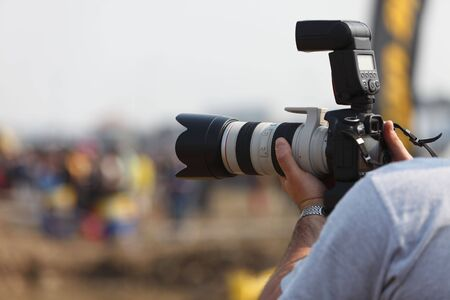 Detail of a photographers hands holding a DSRL camera with a long zoom high end lense attached.