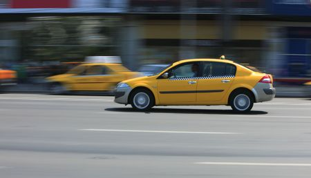 Panning image of a yellow cab in a city street. photo