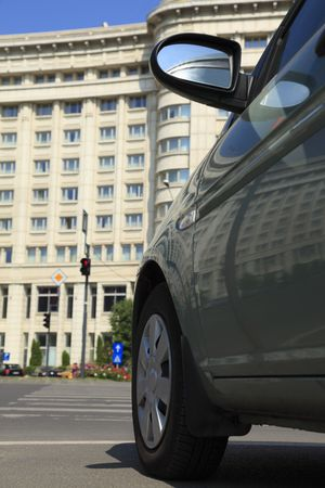 accomodation: Partial image of a car in a city street in front of a big hotel, a good concept for travel and accomodation. Stock Photo