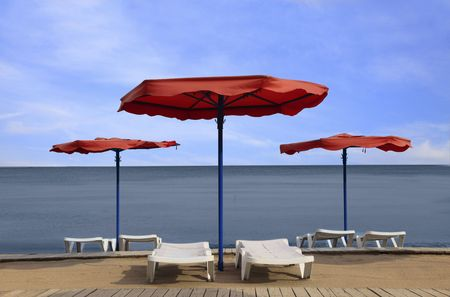 sunbeds: Image of red parasols and white sunbeds on a beach Stock Photo