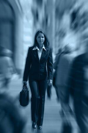 dinamismo: Businesswoman camminare velocemente in un affollato downtown.The immagine presenta un significativo effetto di sfocatura spin per accentuare la dinamicit� della scena. Archivio Fotografico