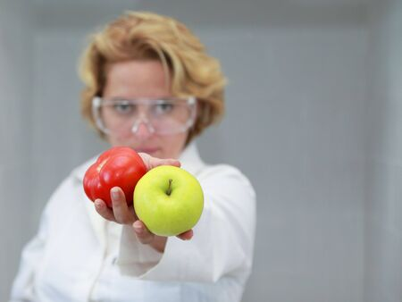 Image of a female researcher offering a tomatoe and an apple to suggest the ideea that healthy eating is recommended also by scientists.Specific lighting for a classical research laboratory. photo