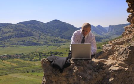 Businessman working on a computer outdoors. photo