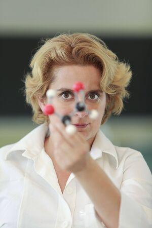 expertize: Female researcher analyzing a molecular model in a laboratory.