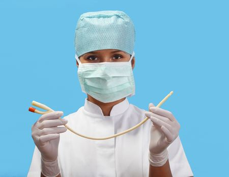 urology: Female nurse holding an urinary catheter isolated against a blue background.