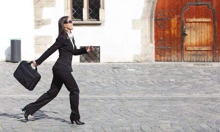 Young businesswoman walking along a cobbled street in front of an old building wall.  photo