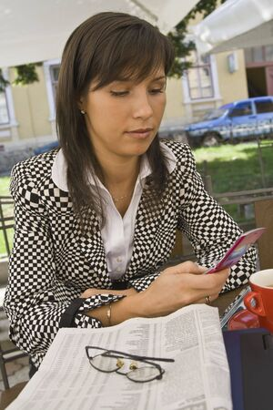 Young businesswoman checking her mobile phone agenda while she is enjoying a morning coffee break on an urban terrace. Stock Photo - 5525018