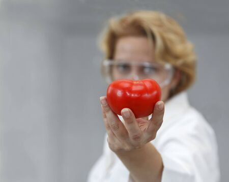 Image of a female researcher offering a tomato and an apple to suggest the idea that healthy eating is recommended also by scientists.Specific lighting for a classical research laboratory. Stock Photo - 5534836