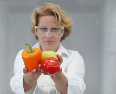Image of a female researcher offering a tomato and an apple to suggest the idea that healthy eating is recommended also by scientists.Specific lighting for a classical research laboratory. Stock Photo - 5534835