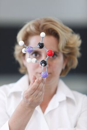 expertize: Female researcher analyzing a molecular model in a laboratory.