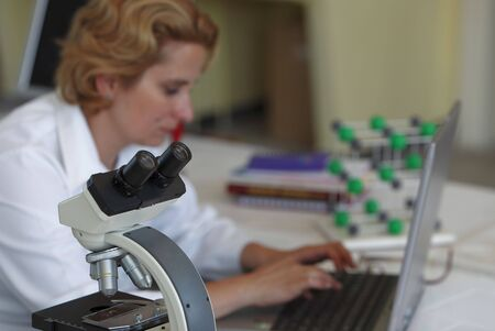 expertize: Image of a researcher working on her workplace in a laboratory.Selective focus on the microscope. Stock Photo