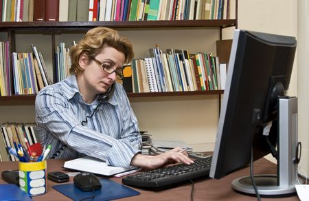 Busy businesswoman at her home business desk. photo