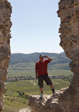 Man scrutinizing the horizon from a rocky fortress ruin in a mountainous area.