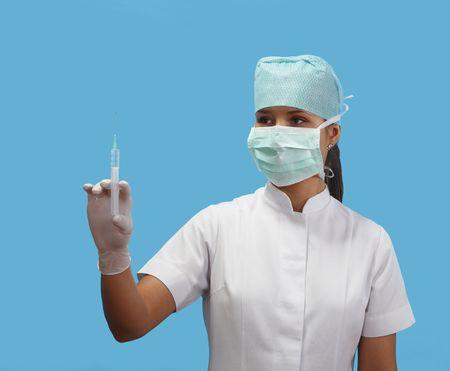 expertize: Female nurse holding a syringe isolated against a blue background.