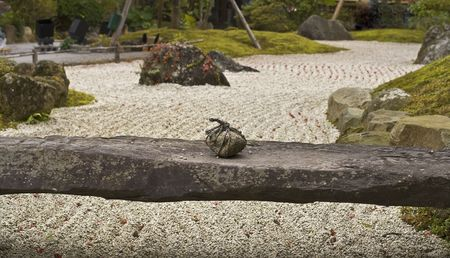 Detail of a traditional Japanese rock garden. This stone braced in strings means Do not enter.  photo