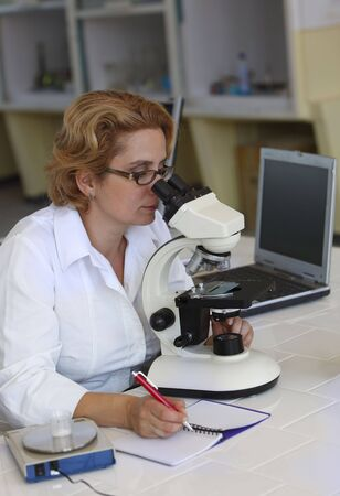 Female researcher taking notices while she is using a microscope. Stock Photo - 5593845