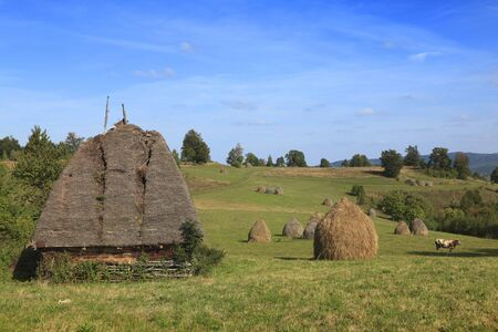 Landscape in an isolated mountainous rural area in Apuseni Mountains, in Transylvania,Romania. The place is known as Motilor country. The house is made exclusively by wood with any pieces of iron. photo