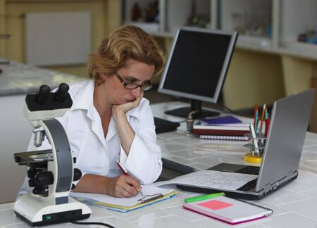 Female researcher taking notices at her workplace in a laboratory.All inscripstions are mine. photo
