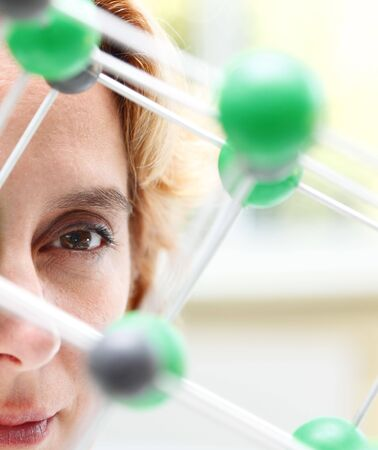 Image of a female researcher eye through a molecular model structure.Selctive focus on the eye. photo