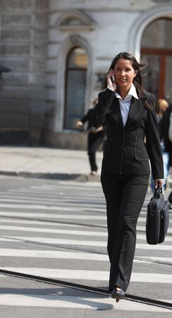 Young businesswoman on the phone crossing the street in a city. photo