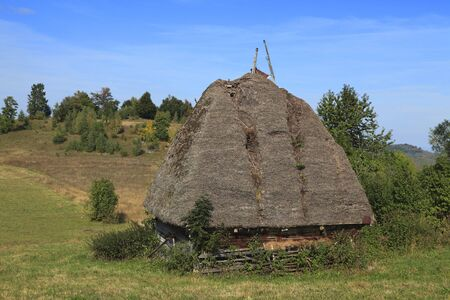 Landscape in an isolated mountainous rural area in Apuseni Mountains in Transylvania Romania. The place is known as Motilor country. The house is made exclusively by wood with any pieces of iron. photo