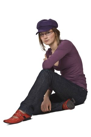 Young woman with glasses and violet hat siting isolated against a white background. photo