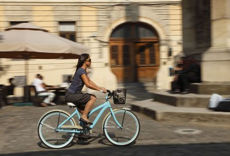 Panning image of a young woman riding her bicycle in a traditional city square.