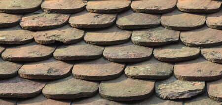 Close-up image of an old roof made of wooden tiles.  photo