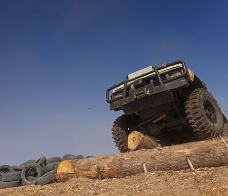 hinder: Off road car passing a tree trunk obstacle during a competition. Stock Photo