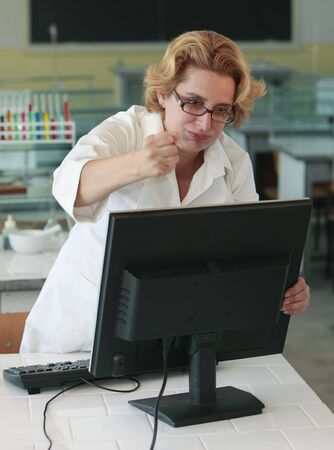 violence in the workplace: Female researcher angry with her computer in the laboratory. Stock Photo