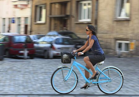 Panning image of a young woman riding her bicycle in a traditional city square. photo
