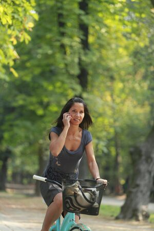 Image of a woman on the phone riding a bicyclein an autumn park photo