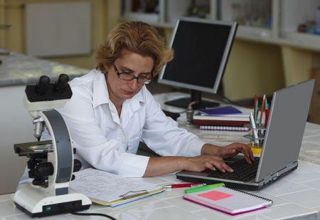 Ricercatore femminile, lavorando su un computer portatile nel suo posto di lavoro in un laboratory.All iscrizioni sono mie.