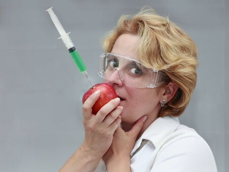 Image of a female researcher trying to eat an apple with a syringe with solution in it. Useful image to suggest the danger of eating genetically transformed food or to promote pure natural food.