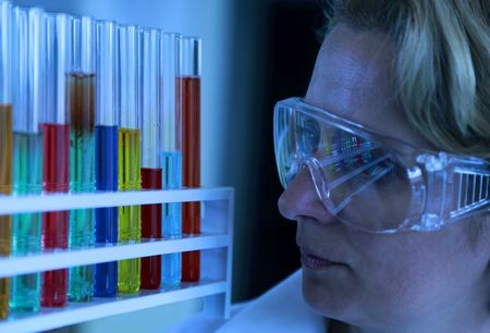 expertize: Female researcher analyzing a rack of test tubes with different solutions in a laboratory.