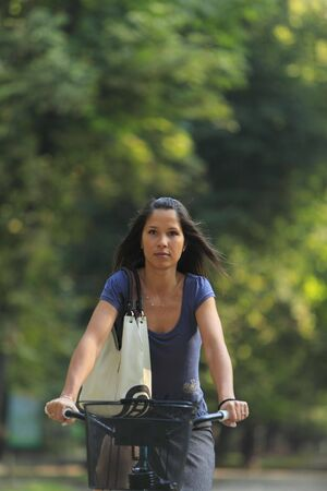 Portrait of a woman riding a bicycle in an autumn park. photo