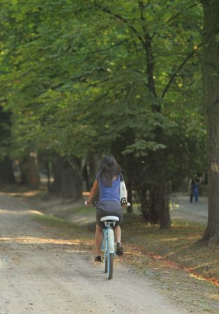 lean back: Young woman riding a bicycle in a park alley.