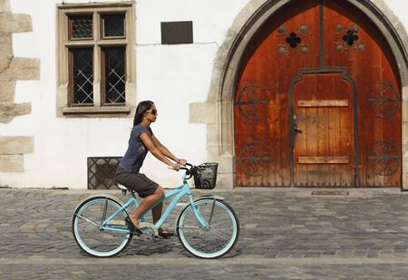 Young woman riding bicycle in front of an old builidng in a city square.