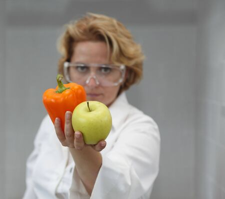 Image of a female researcher offering a tomato and an apple to suggest the idea that healthy eating is recommended also by scientists.Specific lighting for a classical research laboratory. photo