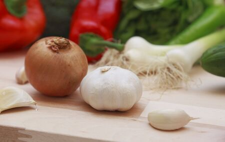 Onion and garlic on a wooden chopping board. photo