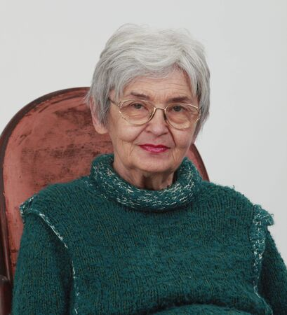 Portrait of an old woman against a grey background photo