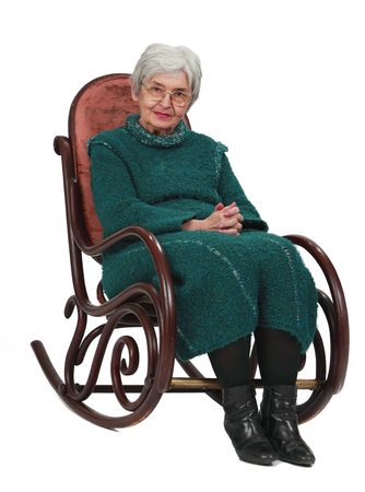 hoary: Old woman sitting on a wooden rocking chair isolated against a white background.