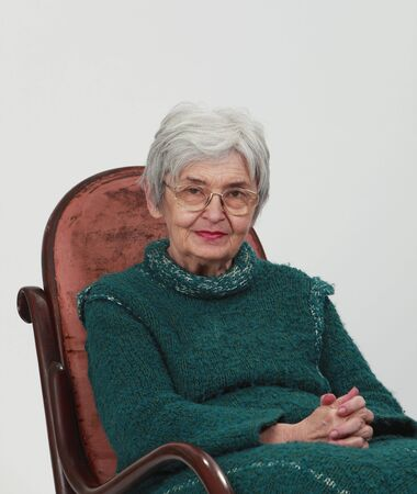Portrait of an old woman sitting on a wooden rocking chair with fingers crossed, against a grey background. photo