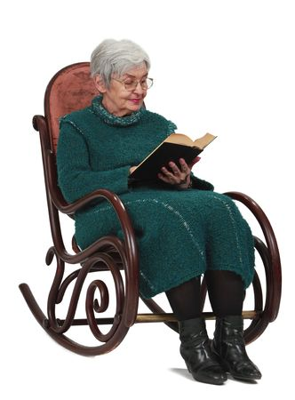 rocking chair: Old woman reading a black book while sitting in a rocker, isolated against a white background.