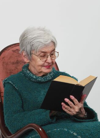 Portrait of an old woman reading a black book against a grey background. photo