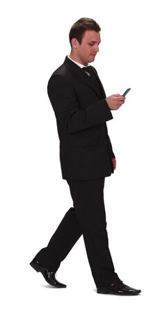 conection: Image of a young businessman walking and checking his mobile phone,isolated against a white background.